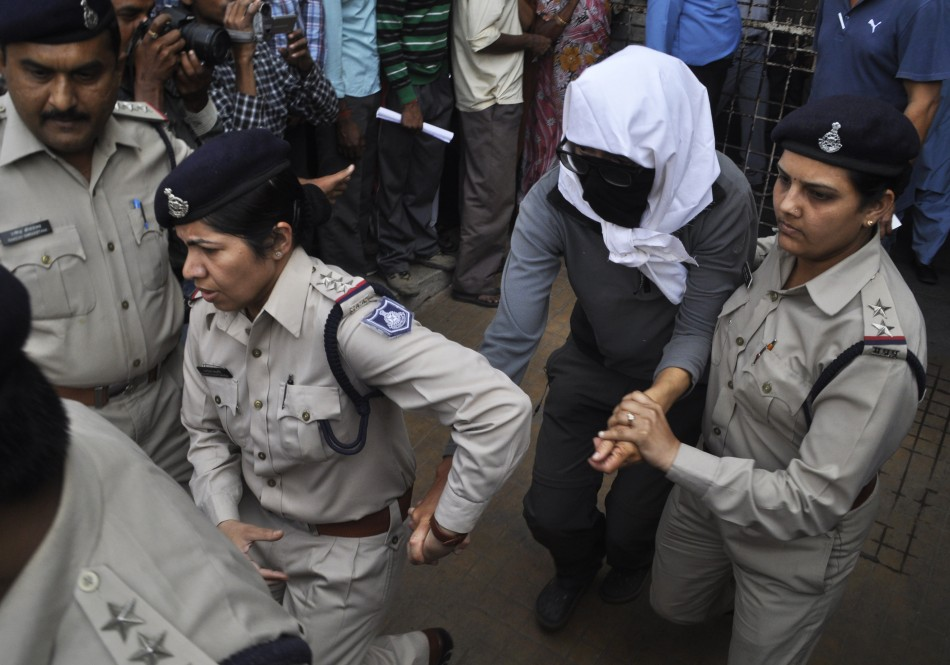 A Swiss woman with her face covered is taken to a hospital by police for her medical examination at Gwalior in the central Indian state of Madhya Pradesh March 16, 2013. Four men raped a 39-year-old Swiss woman camping with her husband in an Indian forest