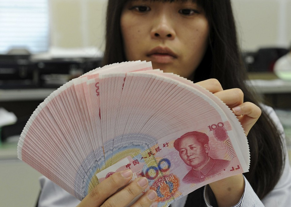 Employee counting Chinese yuan notes in a bank