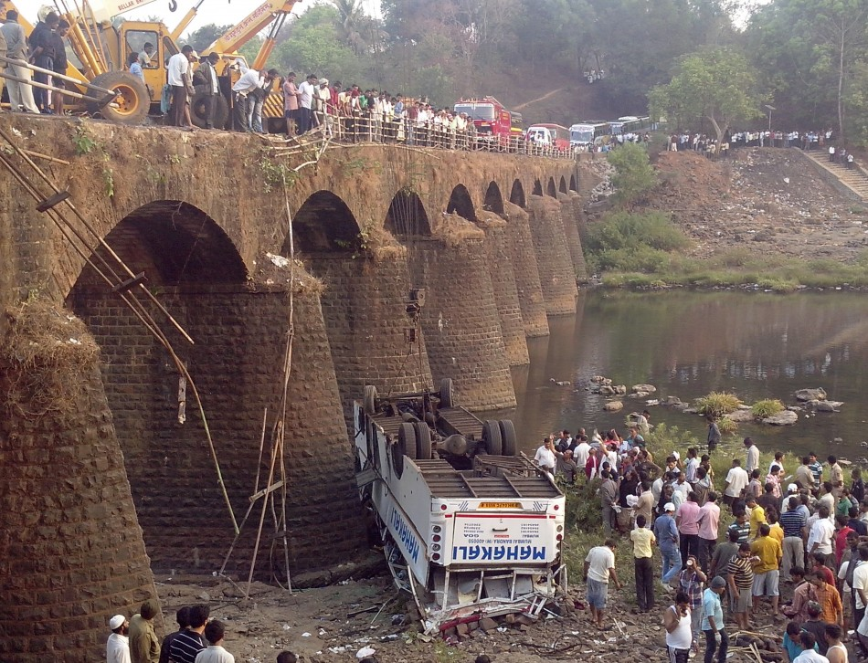 Rescuers and bystanders look at the wreckage of a passenger bus after it fell from a bridge in Ratnagiri district in the western Indian state of Maharashtra