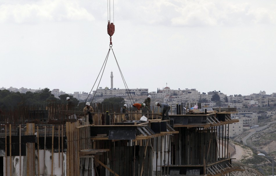 he West Bank town of Bethlehem is seen in the background as Palestinian labourers work on a construction site at a Jewish settlement near Jerusalem known to Israelis as Har Homa and to Palestinians as Jabal Abu Ghneim March 18, 2013. Israel's new housing
