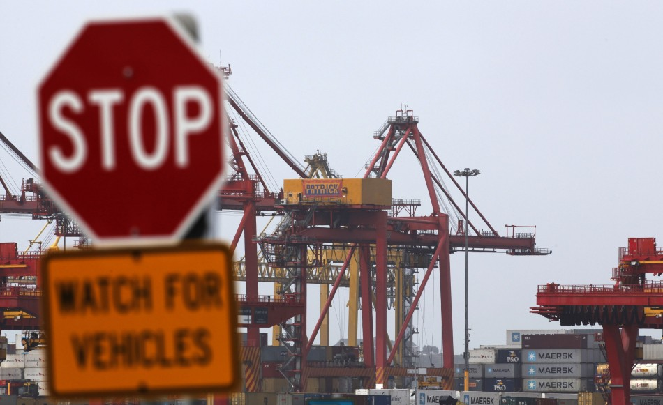A traffic sign stands in front of cranes at the Port of Botany, near Sydney