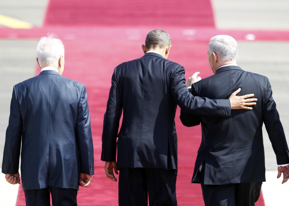 U.S. President Barack Obama (C) walks on the red carpet with Israel's President Shimon Peres (L) and Prime Minister Benjamin Netanyahu (R) during an official welcoming ceremony at Ben Gurion International Airport near Tel Aviv