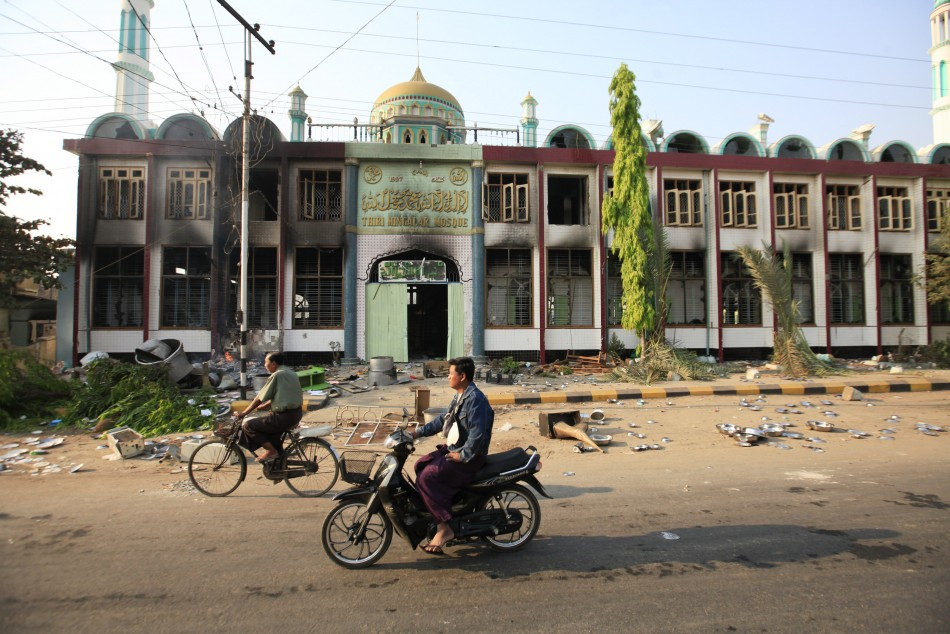 Motorcycles pass in front of a mosque that burned during the riot in Meikhtila March 22, 2013. Unrest between Buddhists and Muslims in central Myanmar has reduced neighbourhoods to ashes and stoked fears that last year's sectarian bloodshed is spreading into the country's heartland in a test of Asia's newest democracy.