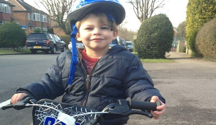 Zachary plays happily on bike near home