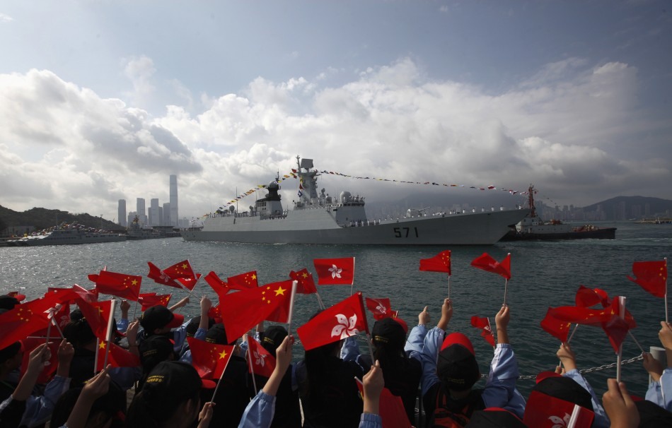 Members of the public wave Chinese and Hong Kong flags as the Chinese naval guided missile frigate Yuncheng (571) arrives at the Ngong Shuen Chau Naval Base in Hong Kong
