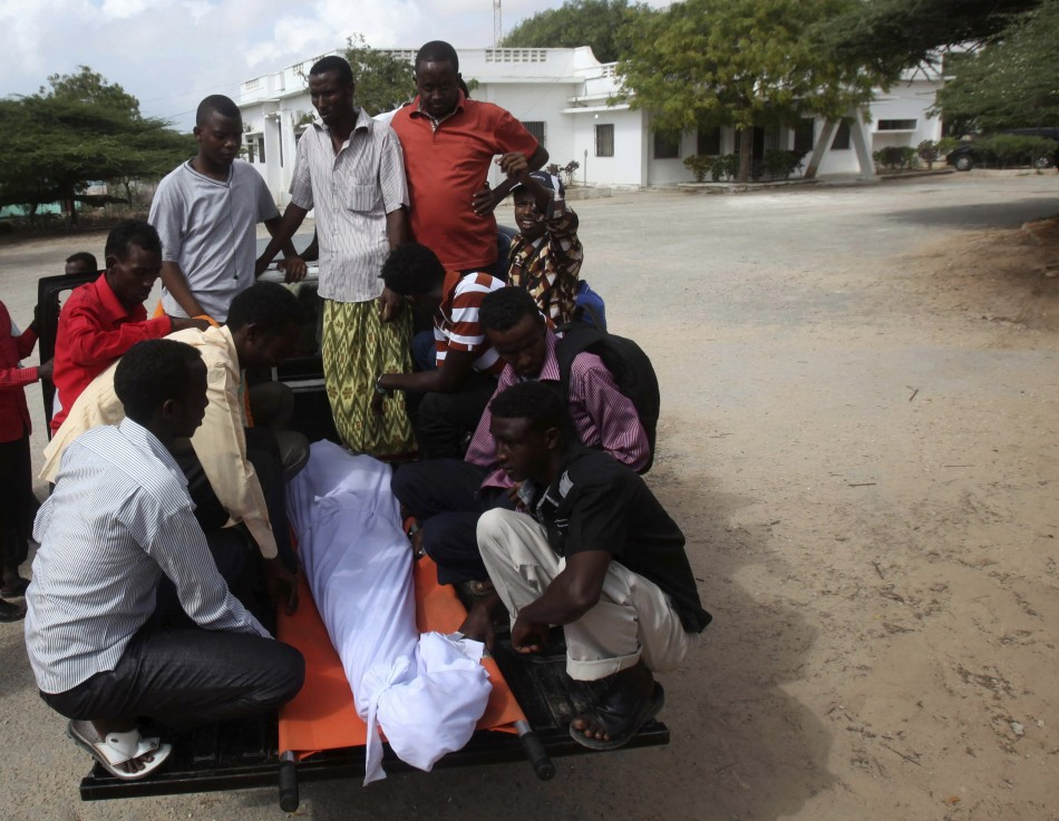 Somali residents arrive with the body of Mohamed Nuxurkey, a local journalist who died in Monday's blast