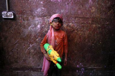 A boy poses for a picture with a water gun during holi celebrations at the Bankey Bihari temple in Vrindavan in the northern Indian state of Uttar Pradesh March 26, 2013. Holi, also known as the Festival of Colours, heralds the beginning of spring and is