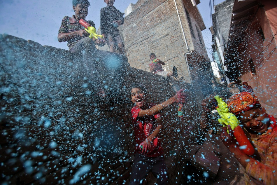 A boy sprays coloured foam during Holi celebrations in a lane near the Bankey Bihari temple in Vrindavan, in the northern Indian state of Uttar Pradesh March 26, 2013. Holi, also known as the Festival of Colours, heralds the beginning of spring and is cel