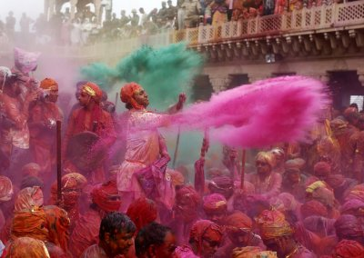 People throw coloured powder as they celebrate Lathmar Holi at Nandgaon village in the northern Indian state of Uttar Pradesh, March 22, 2013. In a Holi tradition unique to Nandgaon and Barsana villages, men sing provocative songs to gain the