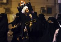 A protester holds up a picture of Sheikh Nemer al-Nemer during a rally at the coastal town of Qatif (Reuters)