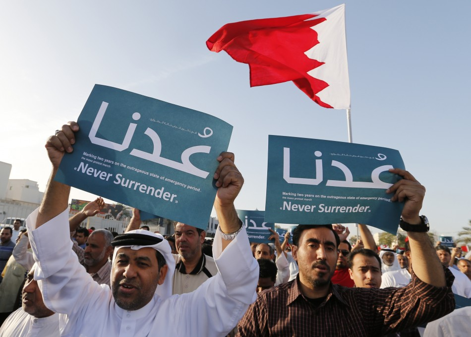 """Anti-government protesters holding banners reading """"Never Surrender"""" march during a demonstration"""