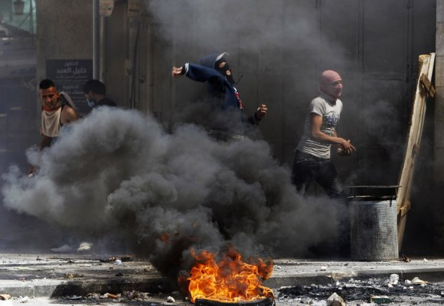 Palestinian protesters throw stones near a burning tyre during clashes with Israeli soldiers in the West Bank city of Hebron, after Maysara Abu Hamdeya