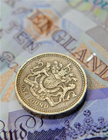 A one pound coin and sterling notes are seen in central London