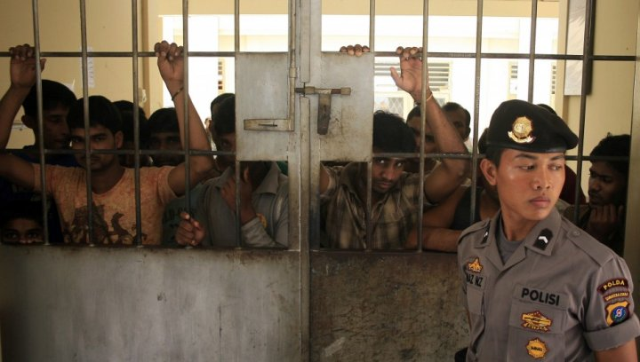 A police officer stands guard near migrants from Myanmar at an immigration detention centre in Medan in Indonesia's North Sumatra