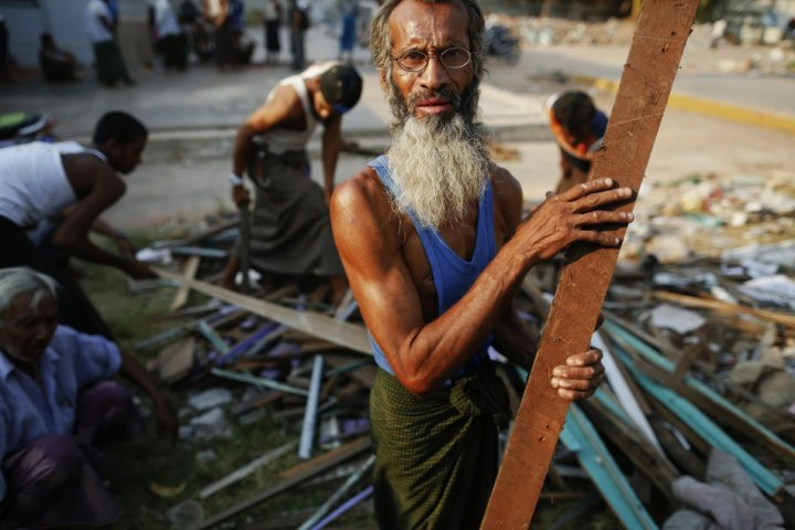 Muslim men clean debris in front of a mosque heavily damaged during recent violence in town of Gyo Bin Gauk