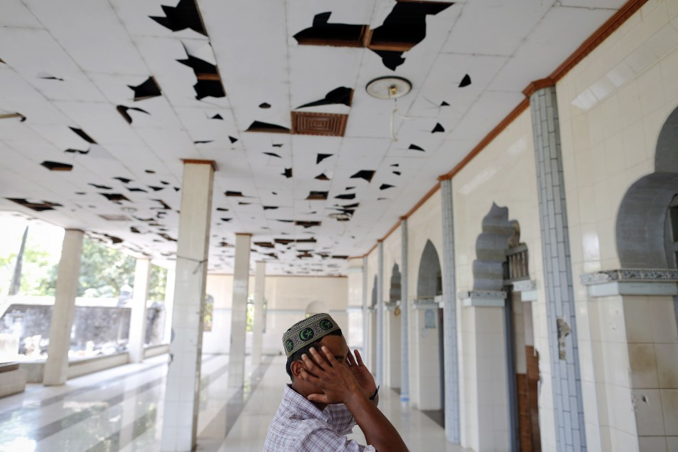 A Muslim man calls for prayers in a mosque damaged during recent violence in town of Minhla