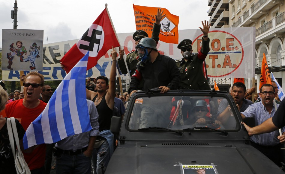Demonstrators, dressed as Nazis, wave a Greek and a swastika flag as they ride in an open-top car in Syntagma Square in Athens as they protest against the visit of Germany's Chancellor Angela Merkel,