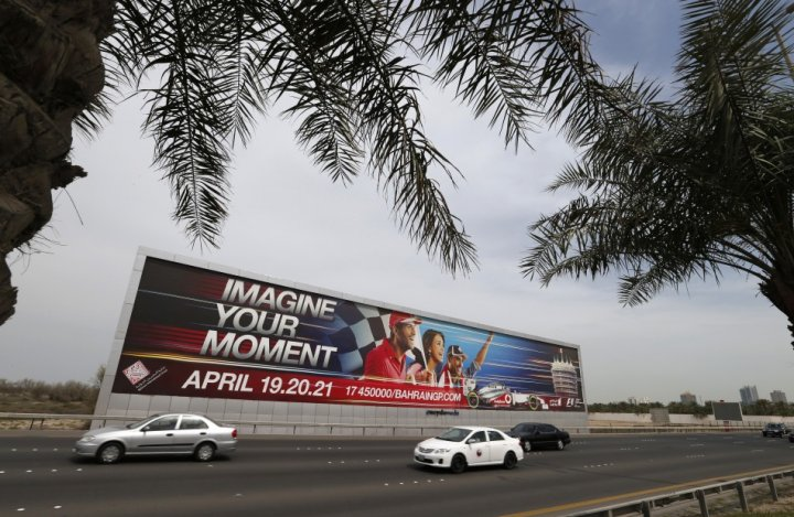Vehicles travel past a large Bahrain Formula One advertising billboard on main highway leading to Bahrain Internaitonal Circuit