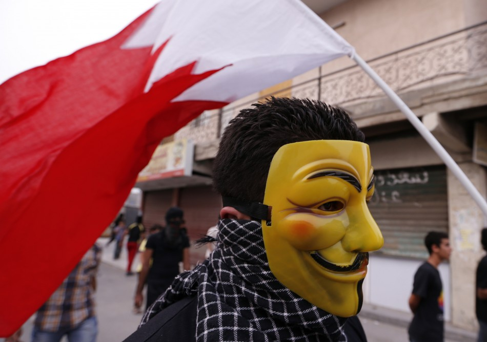 A protester, wearing a Guy Fawkes mask and with the Bahraini flag behind him, participates in an anti-government protest in the village of Diraz