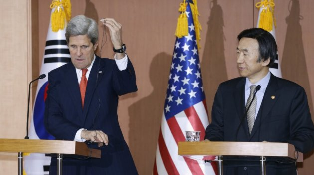 U.S. Secretary of State John Kerry (L) adjusts an earphone during a news conference with South Korean Foreign Minister Yun Byung-se