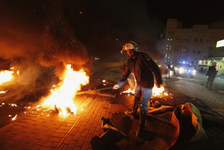 A riot police officer removes burning tyres from the highway set up by anti-government protesters in the village of Dira