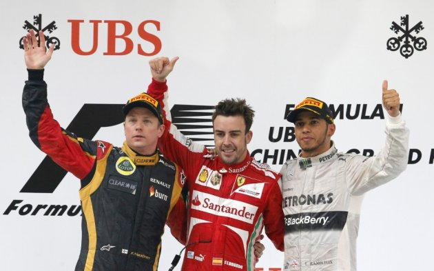Fernando Alonso, flanked by Kimi Raikkonen (L) and Lewis Hamilton