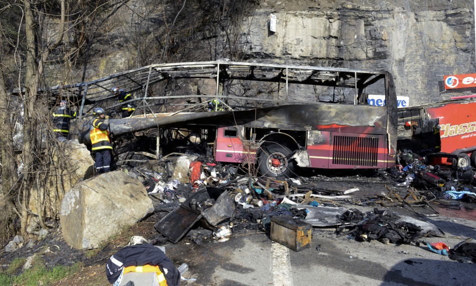 French fire brigade members work around the ruins of a tour bus which crashed and burned on the road from l'Alpe d'Huez in the French Alps (Reuters)