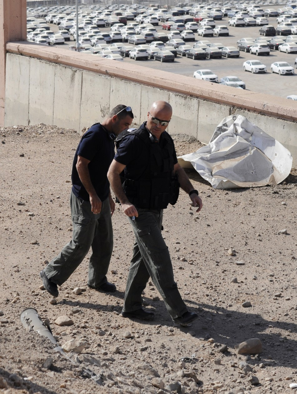 Israeli police explosives experts walk near a rocket which was fired into the Red Sea