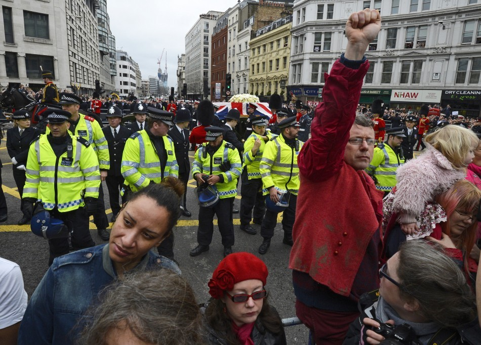Demonstrators turn their backs as the funeral procession of  Margaret Thatcher travels towards St Paul's Cathedral (Reuters)