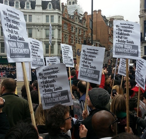 Protesters hold placards with anti-Thatcher statements during the day of her funeral