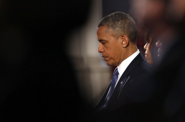 U.S. President Barack Obama and first lady Michelle Obama pray during an interfaith memorial service