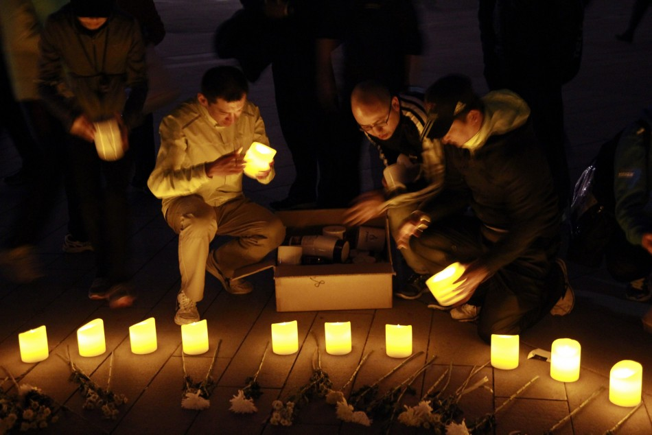 People set up candles and flowers as they pray for victims of Monday's Boston Marathon bombings