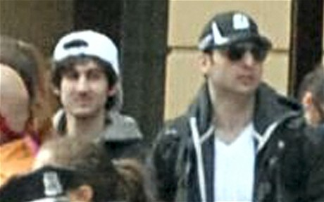 Two suspects wearing baseball caps were caught on CCTV camera minutes before blasts at finish line of Boston marathon.