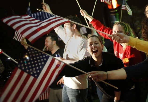 People wave U.S. flags while cheering as police drive down Arlington Street in Watertown, Massachusetts