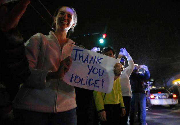 Members of the public cheer as police officers leave the scene where Dzhokhar Tsarnaev, the surviving suspect in the Boston Marathon bombings, was taken into custody