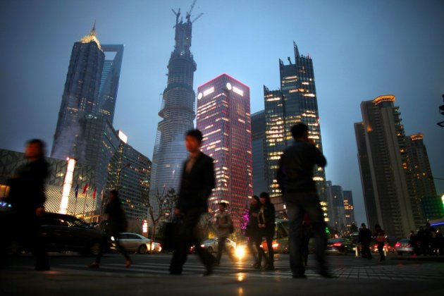 People walk along a busy street at Pudong financial district in Shanghai
