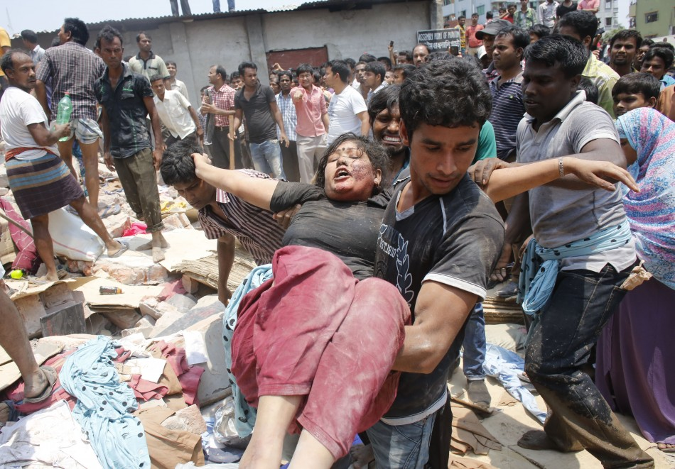 People rescue a garment worker who was trapped under the rubble of the collapsed Rana Plaza building