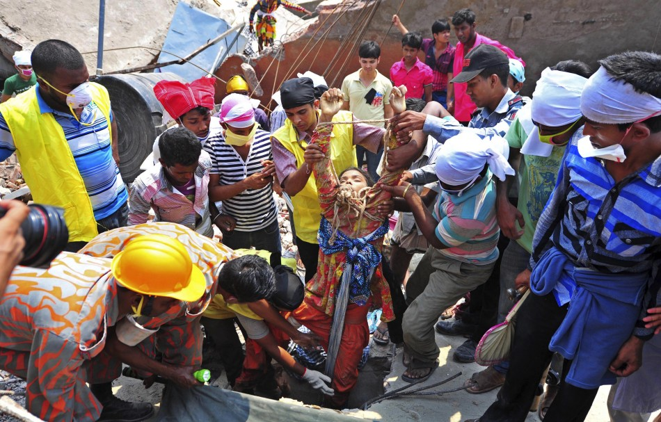 Rescue workers pull a garment worker alive from the rubble of the collapsed Rana Plaza building,