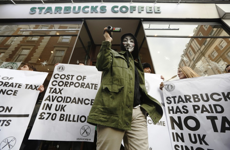 A masked demonstrator leaves a Starbucks outlet in protest against the group's tax practices.