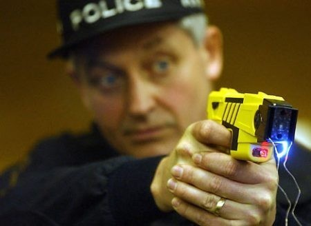 Police demonstrating the Taser gun. (Reuters)