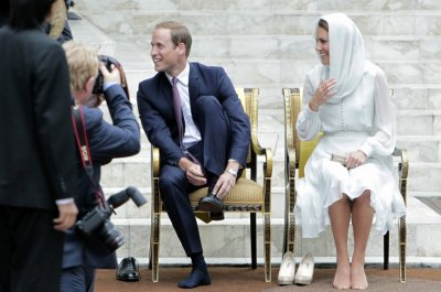Prince William and Catherine, Duchess of Cambridge, take off their shoes before visiting the As-Syakirin Mosque at KLCC in Kuala Lumpur September 14, 2012.