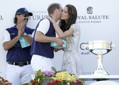 Catherine, the Duchess of Cambridge, kisses her husband, Prince William, while his teammate Santi Trotz L applauds as she presents awards following a polo match at the Santa Barbara Polo and Racquet Club for a charity event held in support of the Americ