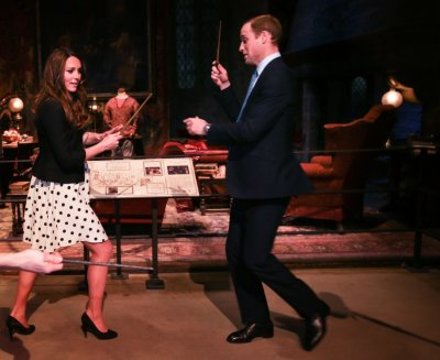 Catherine, Duchess of Cambridge L and her husband Prince William play with magic wands on the set used to depict Diagon Alley in the Harry Potter films, during the inauguration of Warner Bros. Studios Leavesden in London April 26, 2013.