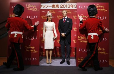 Wax figures of Prince William and his wife Catherine, Duchess of Cambridge, are unveiled by models wearing costumes depicting the Queens guards, during a media briefing for the opening of the Madame Tussauds Tokyo wax museum, in Tokyo November 28, 2