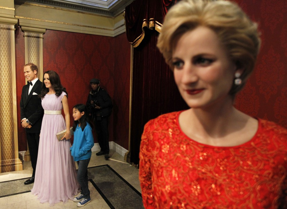 Visitors pose with wax models of Britains Royal couple William and Catherine, the Duke and Duchess of Cambridge, at Madame Tussauds in New York, April 4, 2012.