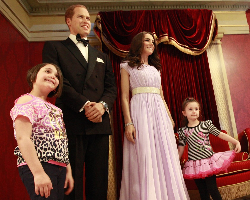 Visitors pose with wax models of royal couple William and Catherine, the Duke and Duchess of Cambridge, at Madame Tussauds in New York, April 4, 2012.