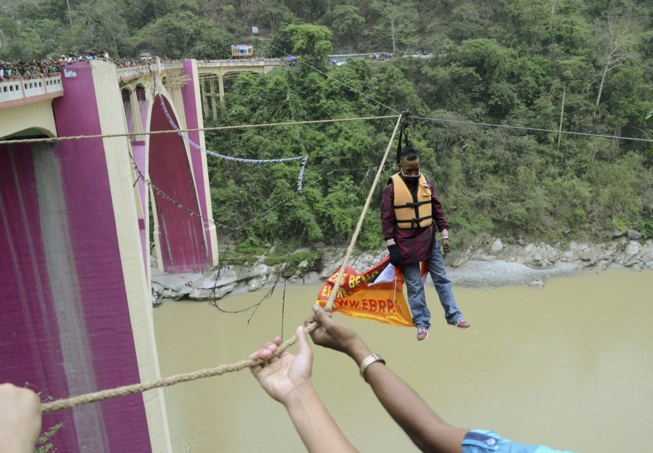 Sailendra Nath Roy, a Guinness World Record holder, is seen hanging from a rope after performing a stunt over the Teesta river