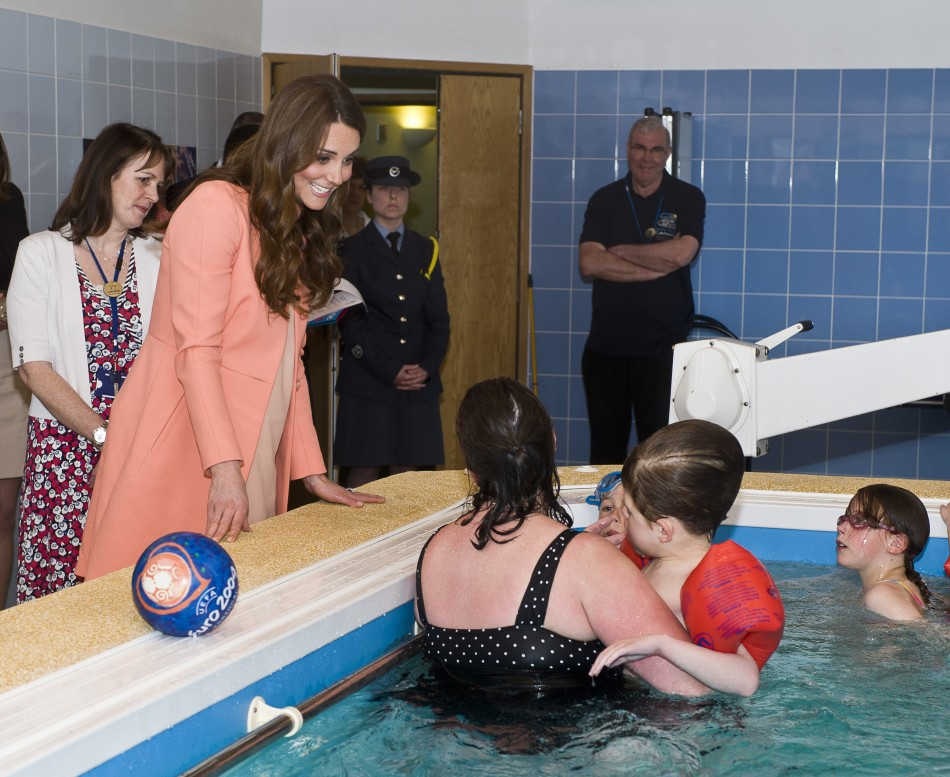 Catherine, Duchess of Cambridge, speaks with staff and children in the hydrotherapy pool
