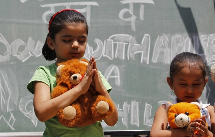 Children pray for the five-year-old victim of a New Delhi attack
