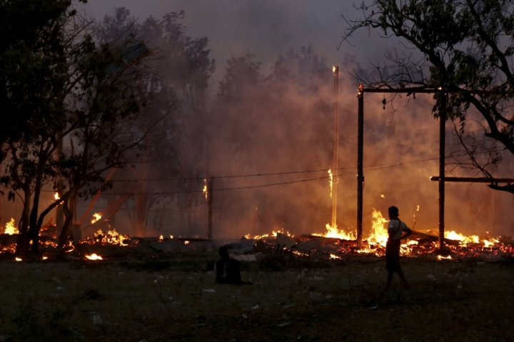 A man looks at buildings on fire during riots at Oakkan village, 100 km (60 miles) north of Yangon